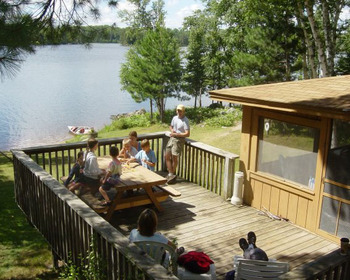 Outdoor deck and exterior view of cabin at River Point Resort & Outfitting Co.