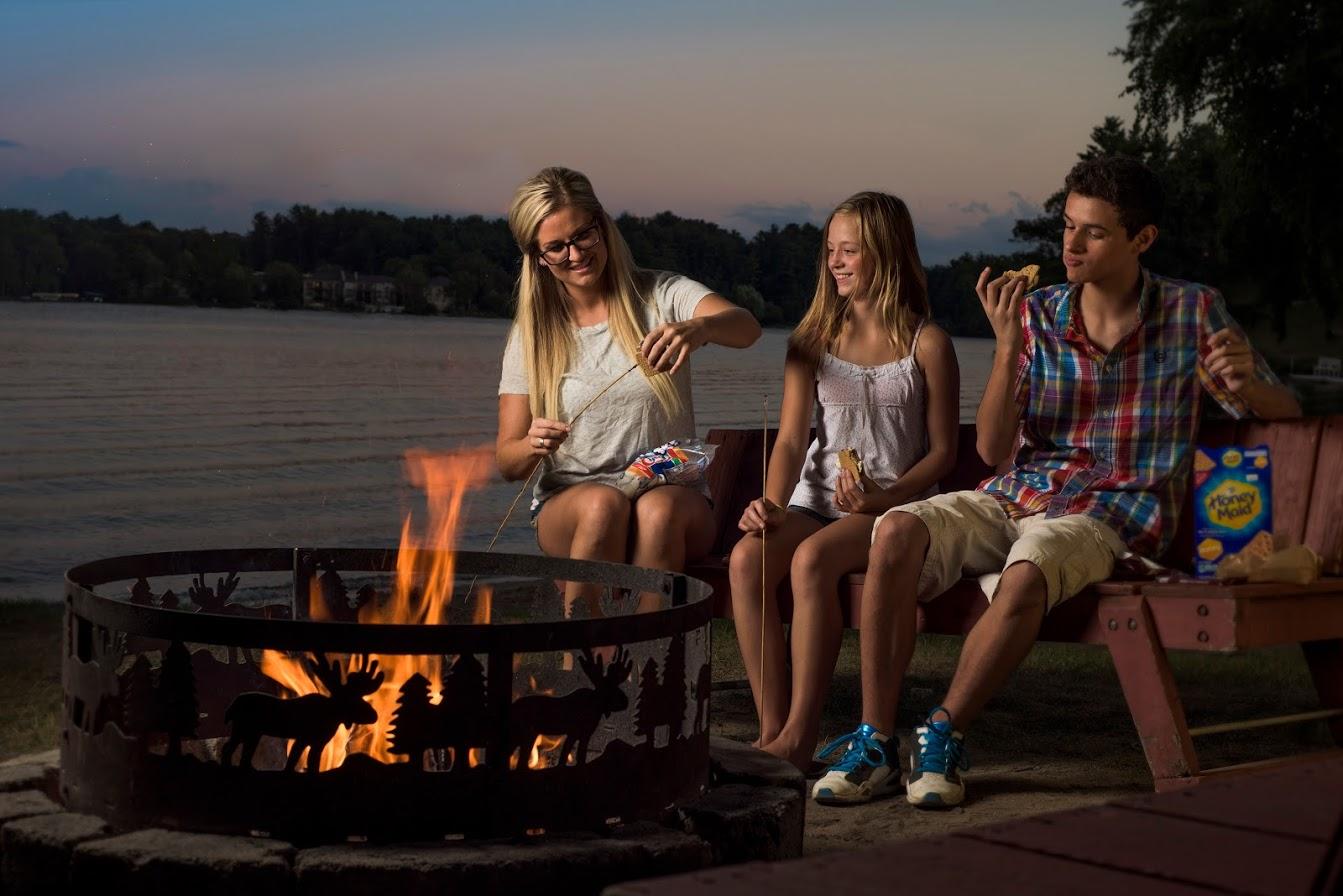 Family at bonfire at Delton Oaks Resort.