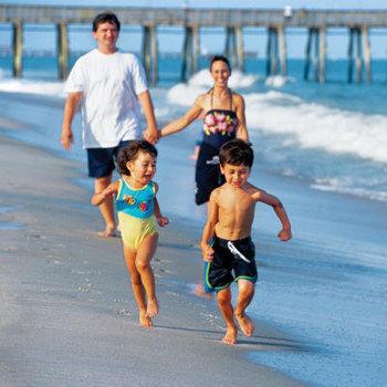 Family on the beach at Caribbean Resort & Villas.