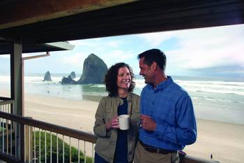 Couple on balcony at Hallmark Resort in Cannon Beach.