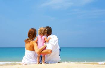 Family on beach at Gulf Blue Vacations.