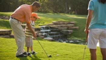 Family playing golf at Hyatt Regency Lost Pines Resort and Spa.