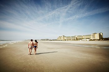 Couple walking on beach at Omni Amelia Island Plantation.