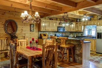Cabin dining table and kitchen at Georgia Mountain Rentals.
