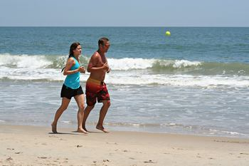 Couple running on the beach near Sea Hawk Motel.