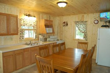 Cabin kitchen and dining table at Bear Paw Resort.