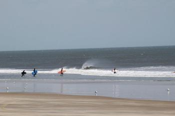 Surfers on the beach at Hilton Suites Ocean City Oceanfront.