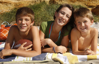 Family on beach at Beachfront Vacation Rentals.