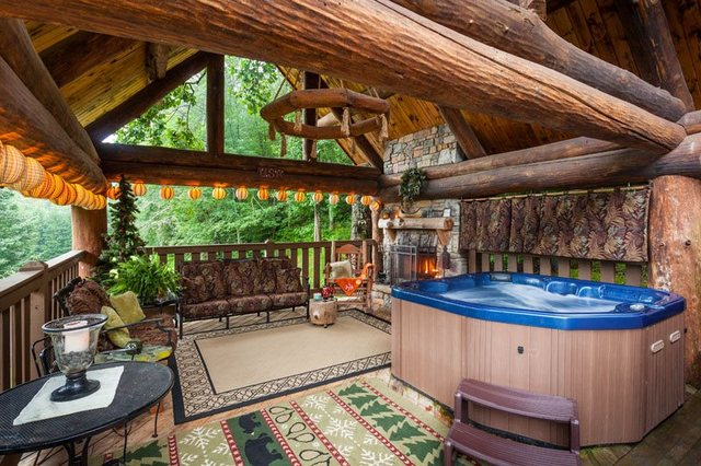 Patio with hot tub at Mountain Oasis Cabin Rentals.
