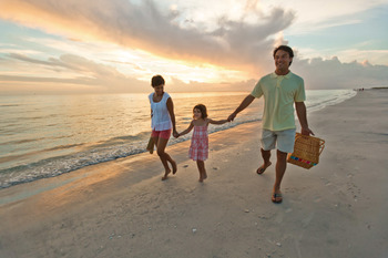 Family on beach at Teeming Vacation Rentals.