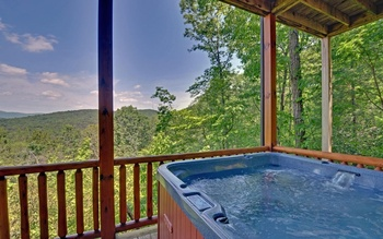 Cabin deck view with jacuzzi from Mountain Top Cabin Rentals.