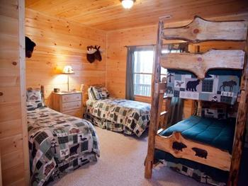 Cabin bedroom with bunk beds at Mountain Getaway Cabin Rentals.