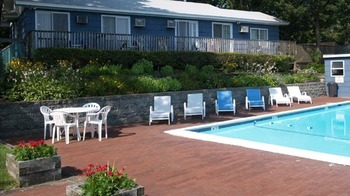 Deck chairs and outdoor pool at Ocean View Terrace Motel.