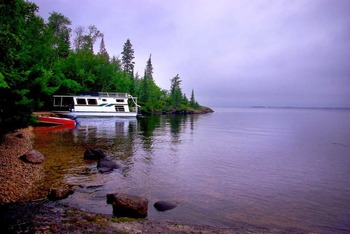 Houseboat docked on a sandy beach at Rainy Lake Houseboats.
